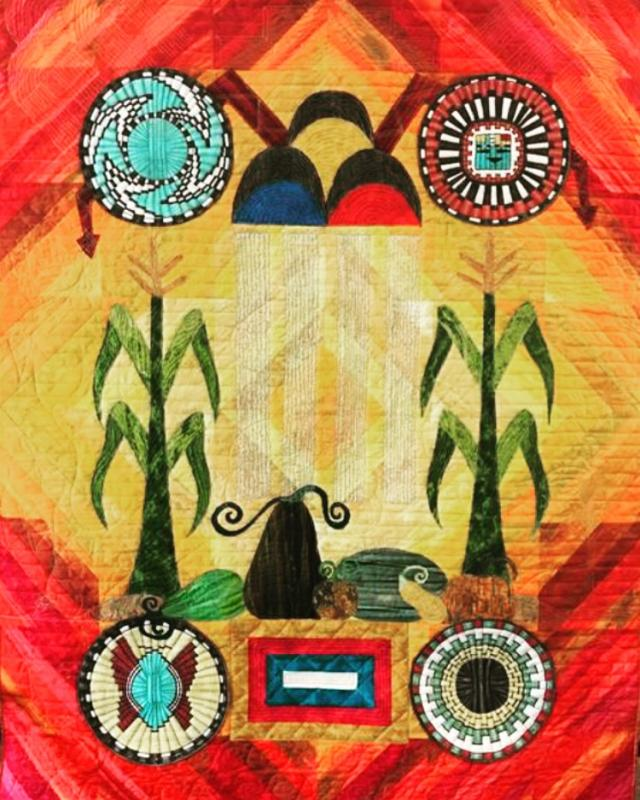 A colorful red, yellow, green, and blue quilt showing crops and Hopi symbols