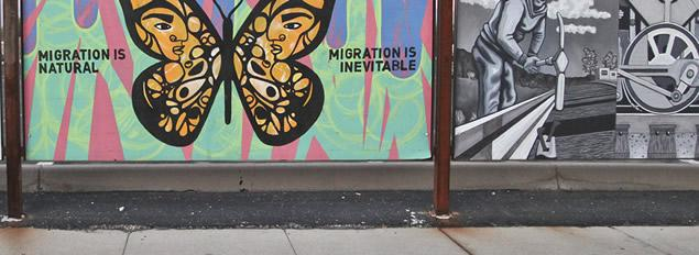Detail from a large mural with a panel supporting immigration and another with a WPA representation of a worker