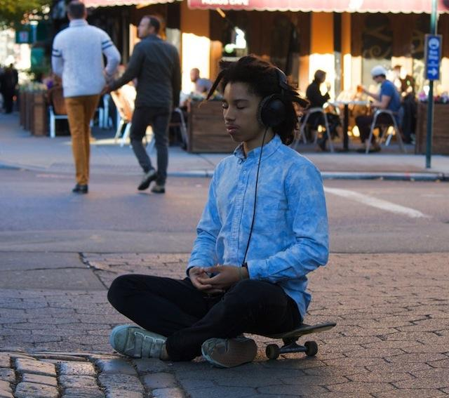 A ypoung in a meditation pose aittiing on a skate board while a number of people go about their business around him.