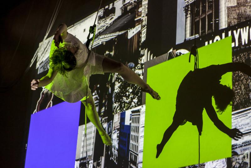 Woman held by ropes dancing on the side of a building with images projected on it.