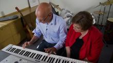 man plays keyboard with music therapist