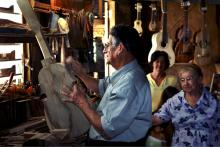 A man works on building a stringed instrument with others behind him watching.