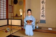A woman in traditional Japanese clothing sits next to tea ware.