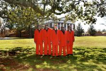 Five men wearing red suits stand outside wearing sunglasses