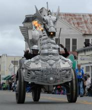 a dragon bicycle sculpture parades down a town's main street