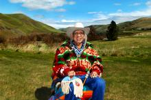 A man in a cowboy hat and colorful jacket sits in an open field.