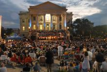 crowd of people sitting and watching evening music concert