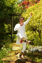 A man dressed in white balances on one leg in a garden.