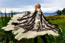 A woman stands in a field twirling while wearing a black and white woven robe.