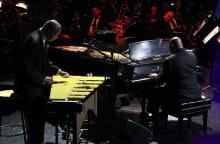 A man performs on the vibraphone next to another man performing on the piano.