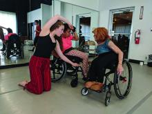 A woman in a wheelchair gives instructions to two younger dancers, one of whom is also in a wheelchair
