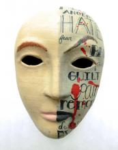 A paper mache mask painted with the words 'hate,' 'guilt,' and 'remorse.'