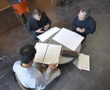 A view from on high of a trio of men sitting around a table looking a music scores