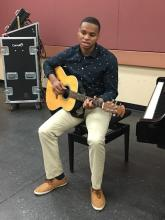 an African American young man sits on a piano stool holding his acoustic guitar