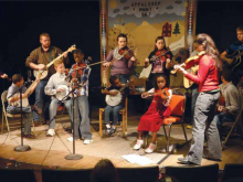 a racially diverse group of young people playing fiddles and banjos on a low stage