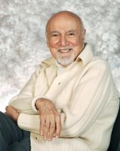 A man in a white sweater sits in a chair facing the camera