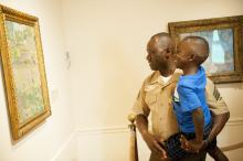 father holds son as both look at a painting in a museum