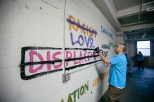In a vacant space, artists spraypaint colorful text on a white cinderblock wall. Words include racism (crossed out), love, displacement crossed out, chain stores, homelessness, affordable rent, and gentrification.