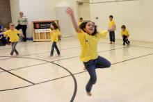 Children wearing t shirts dance in a school recreation room