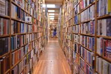 A photo that looks down the aisle of shelves in a bookstore