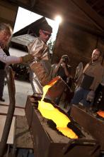 Photo - a woman and man at a glass casting demonstration at the Pilchuck Glass School.