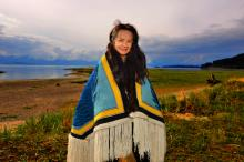 A woman stands on a shore wearing a woven blue and yellow blanket.