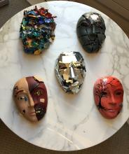 a tabletop laid with 5 different types of masks made in creative arts therapy sessions