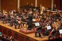 A student orchestra performs on a stage