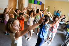 Young children raise their hands above their heads as they take part in a dance class