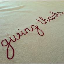"The phrase ""giving thanks"" embroidered in red thread on a white background"