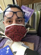 Greg Reiner sits wearing a COVID mask surrounded by playscripts
