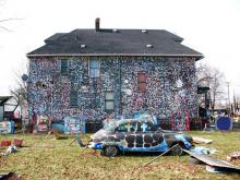 A house covered with colorful polka dots with colorful sculptures made from trash in the front yard
