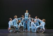 an ensemble of dancers some of whom are in wheelchairs performing on stage