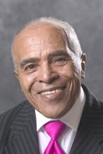 Headshot of a man in a suit and pink tie