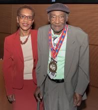 A man in a gray suit wearing a gold medal with a red, blue, and yellow ribbon stands next to a woman in a red suit.