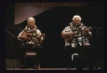 Two men on a stage playing ukuleles and singing.