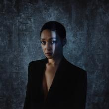 Woman with close-cropped hair in shadows wearing a suit jacket and staring at the camera