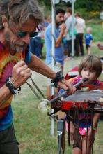 A young girl participates in a glass blowing demonstration with an artist helping.
