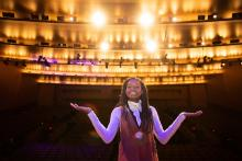 photo of young Black woman with long braids standing on stage with her back to audience and lights blazing behind her