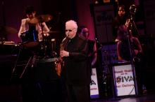 A man in all black wears sunglasses and plays the saxophone on a stage with other musicians behind him.