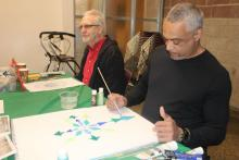 Two older men sit and paint at a table