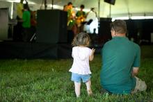 A toddler girl standing in the grass next to her sitting father as they watch an outdoor performance