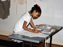 A young girl bends over and decorates an apron as part of an exhibition
