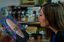 A woman paints a portrait by holding a paintbrush with her mouth