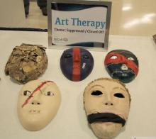 papier mache masks made in art therapy displayed on a table at a Walter Reed event