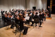 An orchestra sits on stage and performs