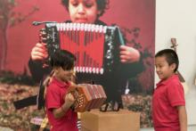 Two young boys play an accordion in front of a large picture of someone playing an accordion