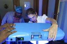 Woman and man looking at phototherapy machinery.