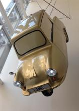 Gold car hanging from ceiling in museum.