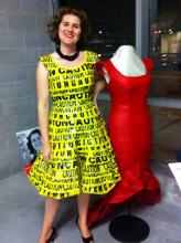 a woman wears a fitted dress made of caution tape and stands next to a dressmakers model wearing a red dress with a scalloped hi lo bottom